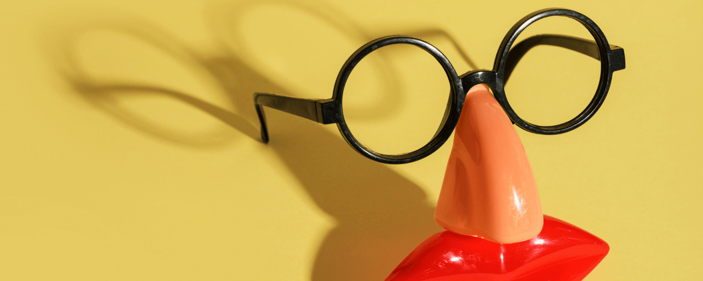 Fake plastic glasses, nose, and lips against a yellow background.
