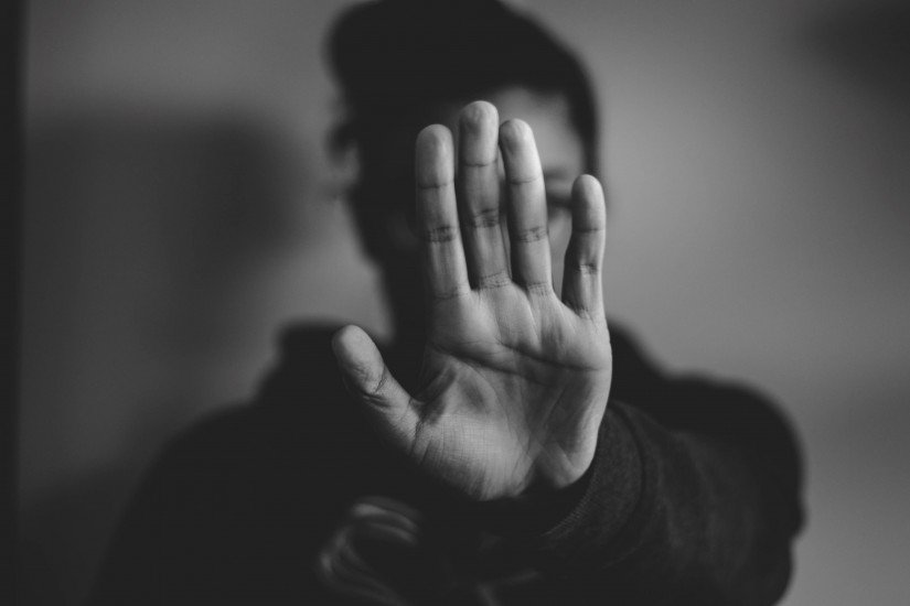 Black and white image of a person holding their palm outstretched, blocking the camera from seeing their face.