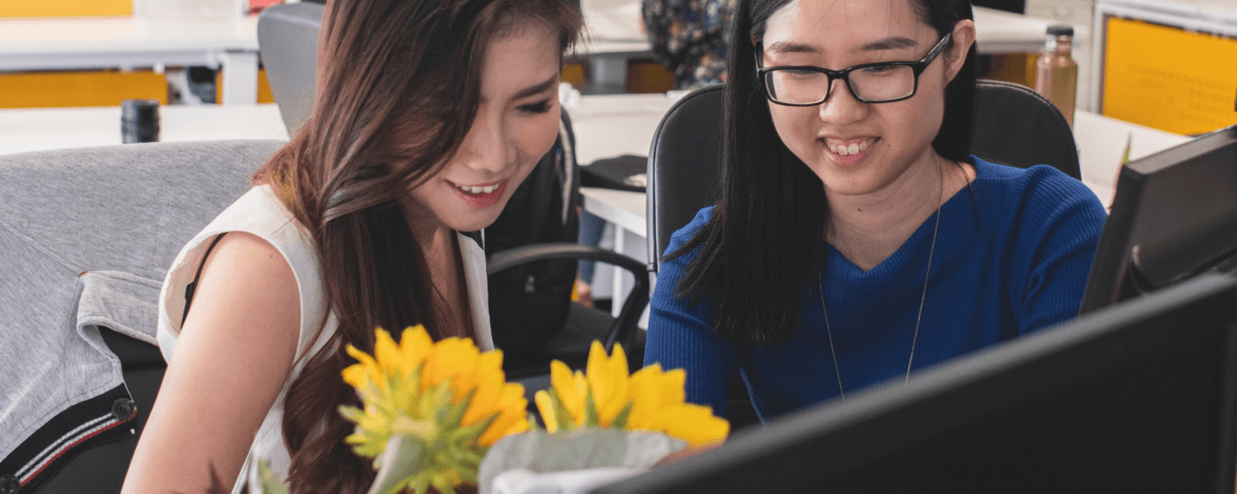 Two young women look at two monitors in an office, smiling.