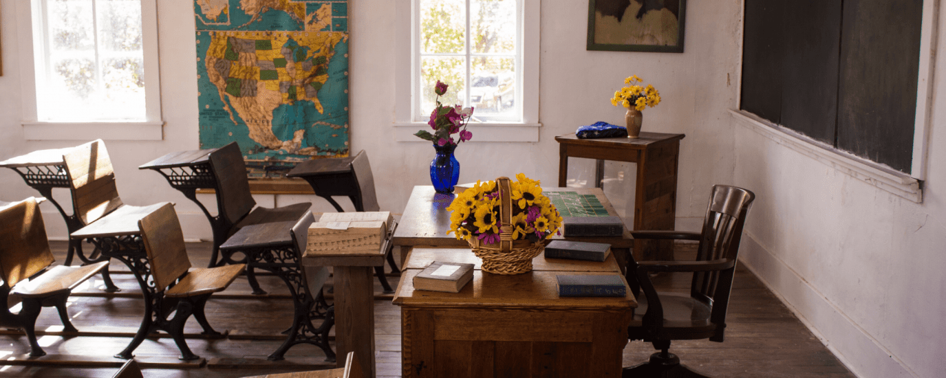 An empty, sunny, old school classroom with a basket of sunflowers on the desk and a chalk board and US map on the wall.