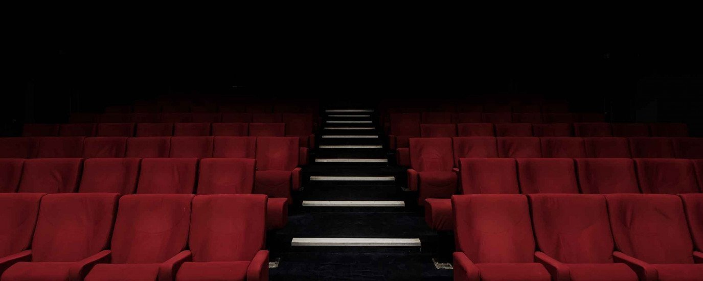 An empty theater with red velvet seats and a staircase up the middle of the two rows.