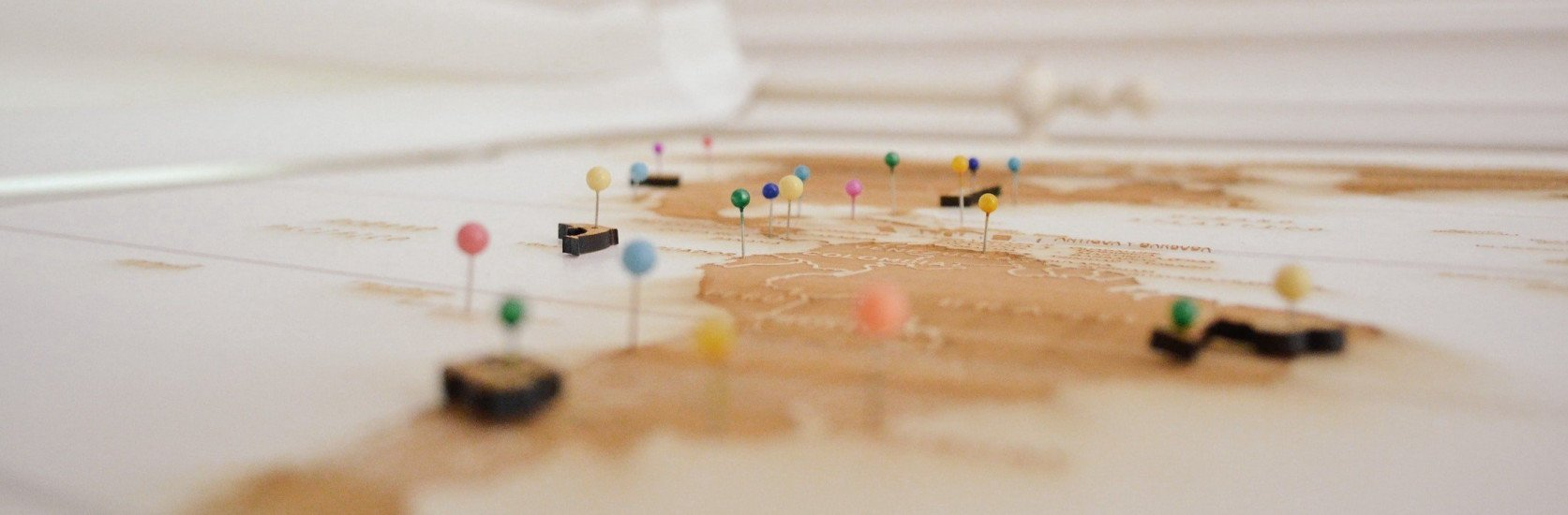 A wooden 2D global map with colorful pins sticking out.