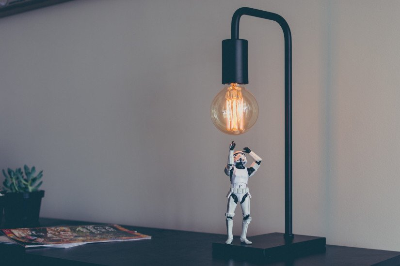 A Star Wars Stormtrooper action-figure stands on a desk, under a lamp, reaching up towards the exposed Edison lightbulb.